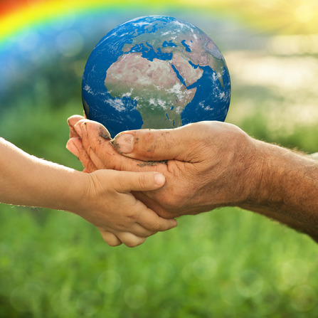 Earth in hands of old man and child against green spring background. Ecology concept